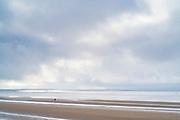 Lone figure walking along sandy beach by the Bristol Channel at Burnham-on-Sea, Somerset, UK