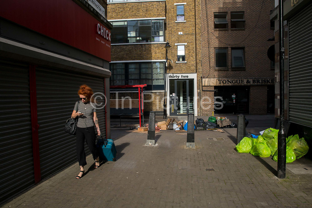 A young woman walks through Hatton Garden whilst looking at her mobile phone on 4th August 2016 in London, United Kingdom. From the series Our Small World, an observation of our mobile phone obsessions