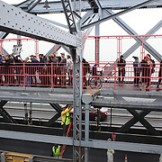 The Occupy Brooklyn protestors march over the Williamsburg Bridge, as workers maintain the bridge below. New York, USA. 1st May 2012. Photo Tim Clayton