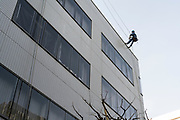 glass cleaner abseiling a building facade Japan Tokyo