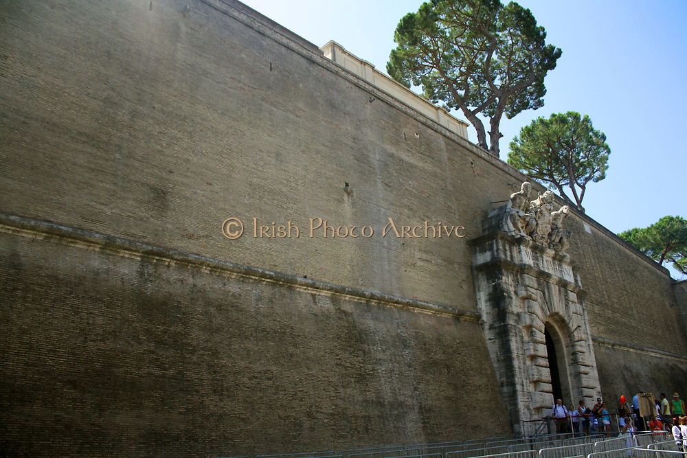 One of the walls around Saint Peter's Square, a large plaza which stands in front of St. Peter's Basilica in the Vatican City, Italy. The wall has a highly decorative entrance with relief work.