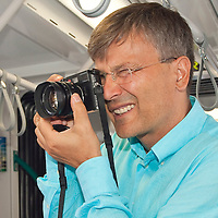Budapest city mayor Gabor Demszky takes photos with his analogue Leica camera on board the newly started Combino tram in Moszkva square, Budapest, Hungary. Saturday, 01. July 2006. ATTILA VOLGYI