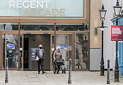 12th, March, 2021. Cheltenham, England. Members of the public exit the Regent Arcade in the town centre wearing masks.
