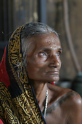 An elderly widow living out her last days near the Manikarnika Ghat, in Varansi, India..Bodies arrive day and night from far and near to be cremated at Jalasi Ghat, the cremation grounds at Manikarnika Ghat. One hundred or more times a day male family members carry a loved one's body through the narrow streets on a bamboo litter to the Ganges River shore?a place of pilgrimage for Hindus during life, and at death. Not every Hindu can be cremated here, because of transportation costs and logistical considerations.