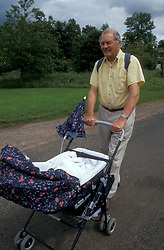 Grandfather pushing his baby grandchild along country road