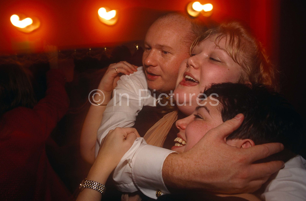 Three friends in their thirties are hugging each other tightly at Coates Wine Bar on London Wall in the City of London, England. We see their three heads as close as possible accompanied by three wall-mounted lights that are glowing a warm red tone making this a cosy and welcoming atmosphere. The man and one of the girls are chubby with round cheeks and chins and so enjoy the good life.