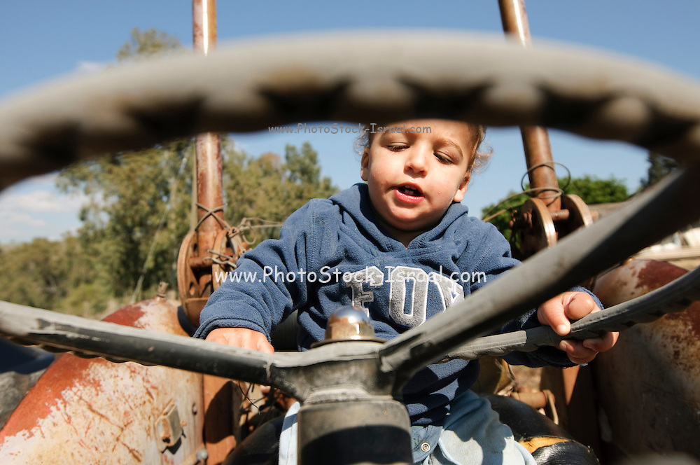 Toddler plays driver on an old tractor