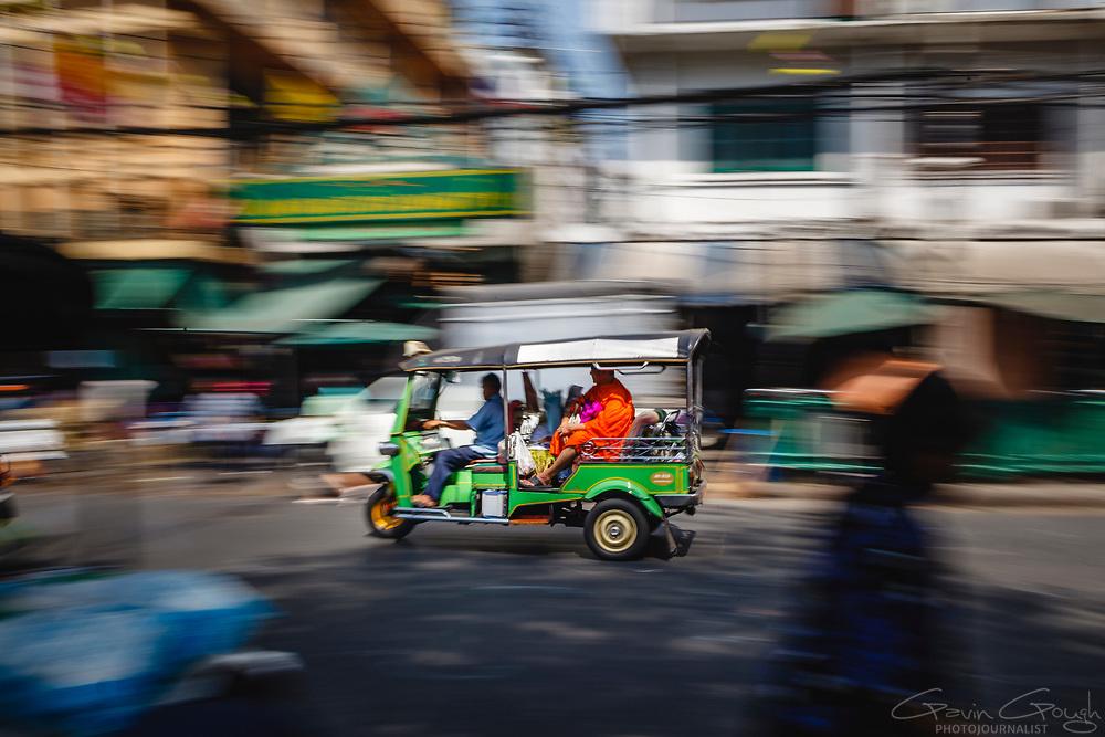A Buddhist monk riding in the back of a tuk-tuk driving through a market street, Pak Khlong Talat, Bangkok, Thailand