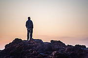 Man viewing sunset on the Pacific Ocean from high on a rock