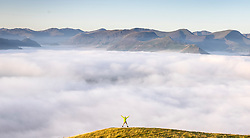 © Licensed to London News Pictures. 07/09/2021. Keswick UK. A man jumps for joy at the top of Latrigg fell in Cumbria at sunrise this morning while looking down on the cloud inversion covering the town of Keswick in the Lake District. Photo credit: Andrew McCaren/LNP
