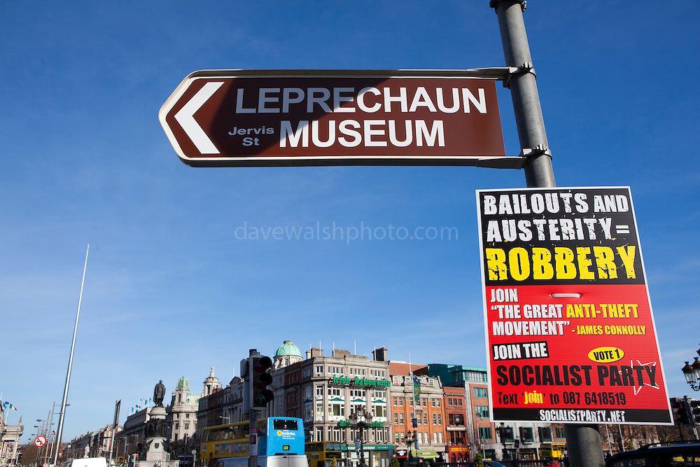Sign for Leprechaun museum, at O'Connell Bridge, Dublin, Ireland, with a Socialist Party poster in the leadup to the 2011 general election, one of the most hotly contested in Ireland's history.