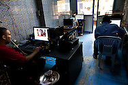 The owner of an internet cafe in Tunis looks at picures of the newly dead Qhadafi on his facebook page. The use of facebook has only increased since the revolution.