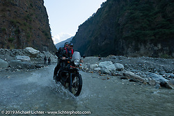 Jason Adamski of New Jersey takes Cool Beans Chris through one of the water crossings on Motorcycle Sherpa's Ride to the Heavens motorcycle adventure in the Himalayas of Nepal. On the sixth day of riding, we went from Tatopani to Pokhara. Saturday, November 9, 2019. Photography ©2019 Michael Lichter.