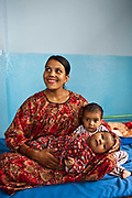 A Nepalese mother sits smiling on a hospital bed with her two children in the Friends of Needy Children Nutritional Rehabilitation Centre, Kathmandu, Nepal.  The centre treats malnourished children and provides education to mothers about nutrition and childcare. Both her children, ages 18 months and 5 months have had nutrition treatment as they were both malnourished.