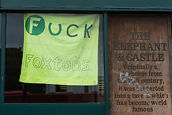 "© Licensed to London News Pictures. 19/06/2015. London, UK. A sign stating ""Fuck Foxtons"" in the window of the Elephant and Castle pub in Southwark, south-east London. A group of activists have occupied the Elephant and Castle pub and are squatting in it to prevent Foxtons Estate Agents from opening an Estate Agent branch. The activists, who are against gentrification want the historic pub site to become a community asset with open use. The Elephant and Castle pub closed earlier this year after its license was revoke and in April, representatives of Foxtons notified planning authorities that they intend to open a branch of the estate agents chain in the pub. Photo credit : Vickie Flores/LNP"