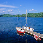 Two sailboats tied to a dock in the Penobscot River. Winterport, Maine