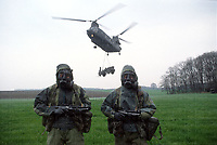 Two soldiers of the British army pose with their STEN submachine guns and NBC uniform while a RAF CH47 Chinook unloads a military tractor into the field below. Photograph by Terry Fincher