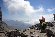 © Licensed to London News Pictures. 17/05/2014. Capel Curig, UK . A man rests near the summit. Walkers climb Snowdon in warm sunshine in North Wales today 17th May 2014. Photo credit : Stephen Simpson/LNP