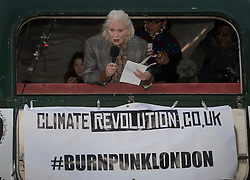 "© Licensed to London News Pictures. 26/11/2016. London, UK. Vivienne Westwood speaks from the back of a bus as Joe Corre (top right), the son of former Sex Pistol manager Malcolm McLaren and Vivienne Westwood burns his personal collection of Sex Pistols punk memorabilia on a boat in the Thames in Chelsea. Earlier this week Joe Corre said that punk has become nothing more than a ""McDonald's brand ... owned by the state, establishment and corporations"". His collection is estimated to be worth £5 million. Photo credit: Peter Macdiarmid/LNP"