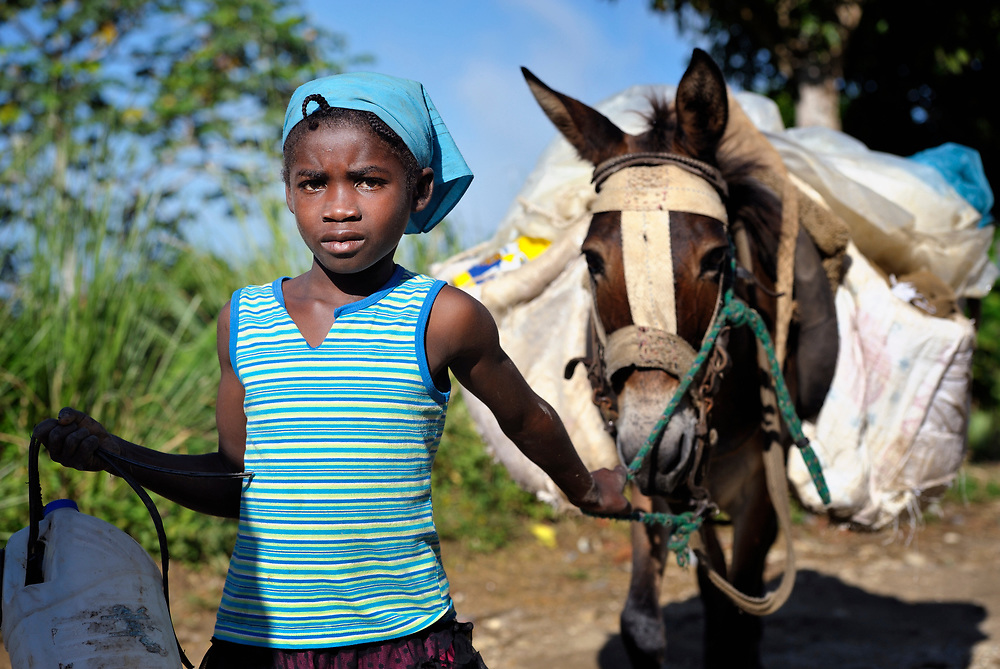 A girl walks along a road with a donkey burdened with goods destined for the market in Les Palmes, a rural village in southern Haiti where the Lutheran World Federation has been working with survivors of the 2010 earthquake, along with other residents, to experience more abundant life.