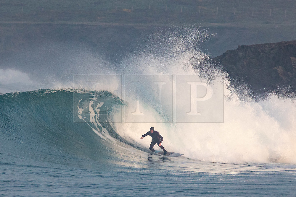 © Licensed to London News Pictures. 24/04/2020. Padstow, UK. A surfer catches a wave just after sunrise near Padstow on the north coast of Cornwall. A period of warm weather is set to continue for the weekend. Photo credit : Tom Nicholson/LNP