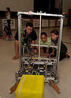 Neal Miller a sophomore at Gilford High School demonstrates how his robot was designed to pick up boxes and move them during the STEAM display night at Gilford Elementary School on Tuesday evening.  (Karen Bobotas/for the Laconia Daily Sun)