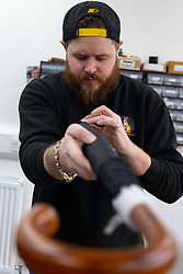Umbrellamaker Lee gives an umbrella a final checkover. Craftspeople at Fox Umbrellas Ltd, a company in Croydon, Surrey, that has been going for over 150 years hand build quality umbrellas. Croydon, Surrey, March 06 2019.