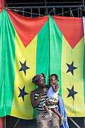 A woman working on her stall in the market, holds her small child in front of two national flags tied together to shield her from the sun, Sao Tome<br /> Sao Tome and Principe, are two islands of volcanic origin lying off the coast of Africa. Settled by Portuguese convicts in the late 1400s and a centre for slaving, their independence movement culminated in a peaceful transition to self government from Portugal in 1975.