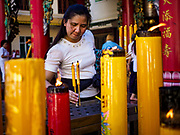 20 OCTOBER 2017 - BANGKOK, THAILAND: A woman lights candles in a Chinese shrine on Yaowarat Roadon the first day of the Vegetarian Festival, what Thais call the Taoist Nine Emperor Gods Festival, in the Chinatown neighborhood of Bangkok, Thailand. It is a nine-day Taoist celebration beginning on the eve of 9th lunar month of the Chinese calendar. For nine days people participating in the festival wear only white and don't eat meat, poultry, seafood, and dairy products. The vegetarian festival is celebrated throughout Thailand, but especially in Phuket and Bangkok, cities with large ethnic Chinese communities.       PHOTO BY JACK KURTZ