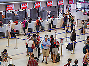 "23 FEBRUARY 2016 - BANGKOK, THAILAND:  People check in for Air Asia flights at Don Mueang Airport. The Thai government has expressed an interest in Thai Airways, Thailand's flag carrier, acquiring a stake in Air Asia (Thailand). Executives from the two companies are expected to meet this week to discuss the proposal. The proposal comes at a time when the Thai aviation industry is facing more scrutiny for maintenance and training of air and ground crews, record keeping, and the condition of Suvarnabhumi Airport, which although less than 10 years old is already over capacity, and facing maintenance issues related to runways and taxiways, some of which have developed cracks. The United States' Federal Aviation Administration late last year downgraded Thailand to a ""category 2"" rating, which means its civil aviation authority is deficient in one or more critical areas or that the country lacks laws and regulations needed to oversee airlines in line with international standards. Thai Airways, the flag carrier, has also faced a challenge with declining profits and alleged mismanagement. Air Asia is one of the most successful budget carriers in Asia.        PHOTO BY JACK KURTZ"