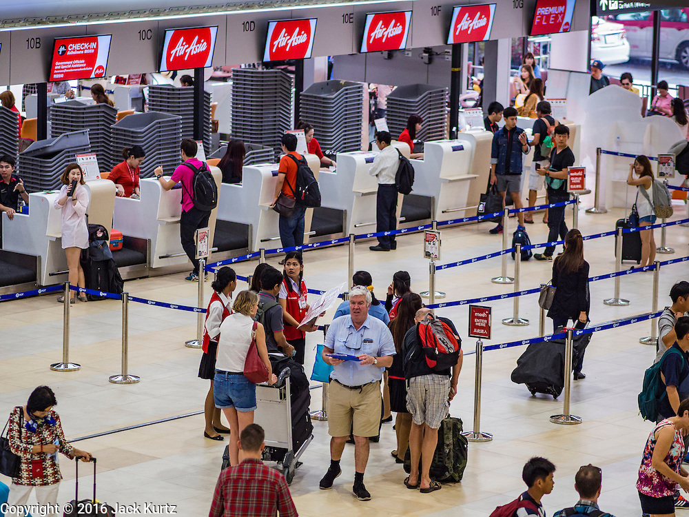 """23 FEBRUARY 2016 - BANGKOK, THAILAND:  People check in for Air Asia flights at Don Mueang Airport. The Thai government has expressed an interest in Thai Airways, Thailand's flag carrier, acquiring a stake in Air Asia (Thailand). Executives from the two companies are expected to meet this week to discuss the proposal. The proposal comes at a time when the Thai aviation industry is facing more scrutiny for maintenance and training of air and ground crews, record keeping, and the condition of Suvarnabhumi Airport, which although less than 10 years old is already over capacity, and facing maintenance issues related to runways and taxiways, some of which have developed cracks. The United States' Federal Aviation Administration late last year downgraded Thailand to a """"category 2"""" rating, which means its civil aviation authority is deficient in one or more critical areas or that the country lacks laws and regulations needed to oversee airlines in line with international standards. Thai Airways, the flag carrier, has also faced a challenge with declining profits and alleged mismanagement. Air Asia is one of the most successful budget carriers in Asia.        PHOTO BY JACK KURTZ"""