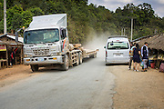 12 MARCH 2013 - ALONG HIGHWAY 13, LAOS: A truck passes through a Hmong community on Highway 13 in rural Laos. The paving of Highway 13 from Vientiane to near the Chinese border has changed the way of life in rural Laos. Villagers near Luang Prabang used to have to take unreliable boats that took three hours round trip to get from the homes to the tourist center of Luang Prabang, now they take a 40 minute round trip bus ride. North of Luang Prabang, paving the highway has been an opportunity for China to use Laos as a transshipping point. Chinese merchandise now goes through Laos to Thailand where it's put on Thai trains and taken to the deep water port east of Bangkok. The Chinese have also expanded their economic empire into Laos. Chinese hotels and businesses are common in northern Laos and in some cities, like Oudomxay, are now up to 40% percent. As the roads are paved, more people move away from their traditional homes in the mountains of Laos and crowd the side of the road living off tourists' and truck drivers.    PHOTO BY JACK KURTZ