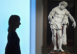 © Licensed to London News Pictures. 01/12/2011, London, UK.  A Bonhams employee look at  a very rare 82cm high porcelain figure of Hercules created at the Doccia factory in Tuscany in 1753-55 is to be sold at Bonhams, New Bond Street, London on 7th December 2011.  This is the first time that a Doccia figure of this size has come to auction and the piece is estimated to sell for £300,000-500,000.. Photo credit : Stephen Simpson/LNP