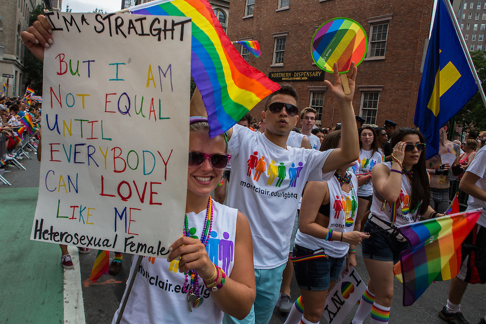 "A woman from Montclair State University carries a sign that reads ""I'm straight but I am not equal until everybody can love like me  / heterosexual female."" There were many straight supporteers of the gay community in the march and in the spectators."