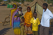 Abdel Karim Aboubakar's mother D'jimia Ishakh Souleymane, 40, holds his youngest sister, Hawa, 2 inside the Breidjing Refugee Camp in Eastern Chad. (Abdel Karim Aboubakar is featured in the book What I Eat: Around the World in 80 Diets.) The Aboubakar family from Darfur province, Sudan, which lives in the camp, is one of the thirty families featured with a weeks' worth of food in the book Hungry Planet: What the World Eats. The family consists of D'jimia Ishakh Souleymane, 40, Abdel Kerim, 16, Acha, 12, Youssouf, 8, Mariam, 5, and Hawa, 2. MODEL RELEASED.