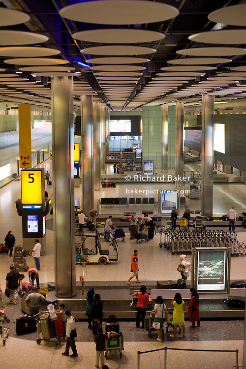 Wide aerial view of passengers awaiting baggage in the baggage reclaim hall in the arrivals of Heathrow Airport's T5
