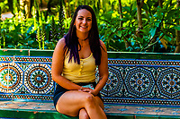 Young woman sitting on a tiled bench in the gardens of The Alcázar of Seville (Real Alcazar) is a royal palace in Seville, Spain, built for the Christian king Peter of Castile.