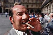 Bald gypsy man smoking a cigar in the Plaza Mayor in Salamanca, Spain.