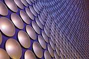 Façade of Birmingham's Selfridges store at night. The skin consists of thousands of spun, anodised aluminium discs that reflect the surrounding city, set against a blue curved, sprayed concrete wall. Architect: Future Systems. Engineer: Arup. Birmingham, UK, 2007