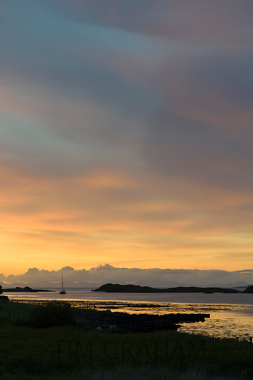 Skyscene of setting sun over solitary fishing boat on Dunvegan Loch, the Isle of Skye in Scotland