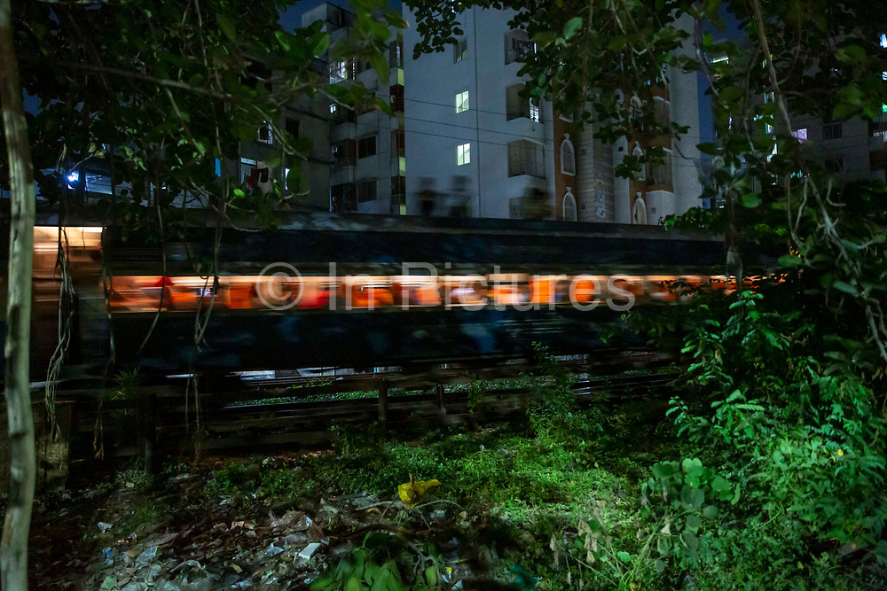 A train passing along the track at night between Dhaka and Tejgaon in the Tejgaon railway district on the 23rd of September 2018 in Dhaka, Bangladesh.