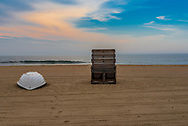 An empty life guard chair and boat on the beach early in the morning