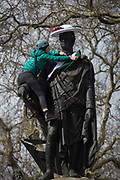 A womens group member drapes a suffragette-style sash across the statue of Francis, Duke of Bedford on International Womens Day, on 8th March 2018, in Russell Square, London, England. According to the group concerned about the poor representation of women commemorations, there are fewer than 3% of non-royal statues in the UK. Francis Russell, 5th Duke of Bedford 1765-1802 was an English aristocrat and Whig politician, responsible for much of the development of central Bloomsbury, London.
