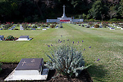 Graves of fallen servicemen and servicewomen with the Cross of Sacrifice during the Remembrance Sunday ceremony at the Hodogaya, Commonwealth War Graves Cemetery in Hodogaya, Yokohama, Kanagawa, Japan. Sunday November 11th 2018. The Hodagaya Cemetery holds the remains of more than 1500 servicemen and women, from the Commonwealth but also from Holland and the United States, who died as prisoners of war or during the Allied occupation of Japan. Each year officials from the British and Commonwealth embassies, the British Legion and the British Chamber of Commerce honour the dead at a ceremony in this beautiful cemetery. The year 2018 marks the centenary of the end of the First World War in 1918.