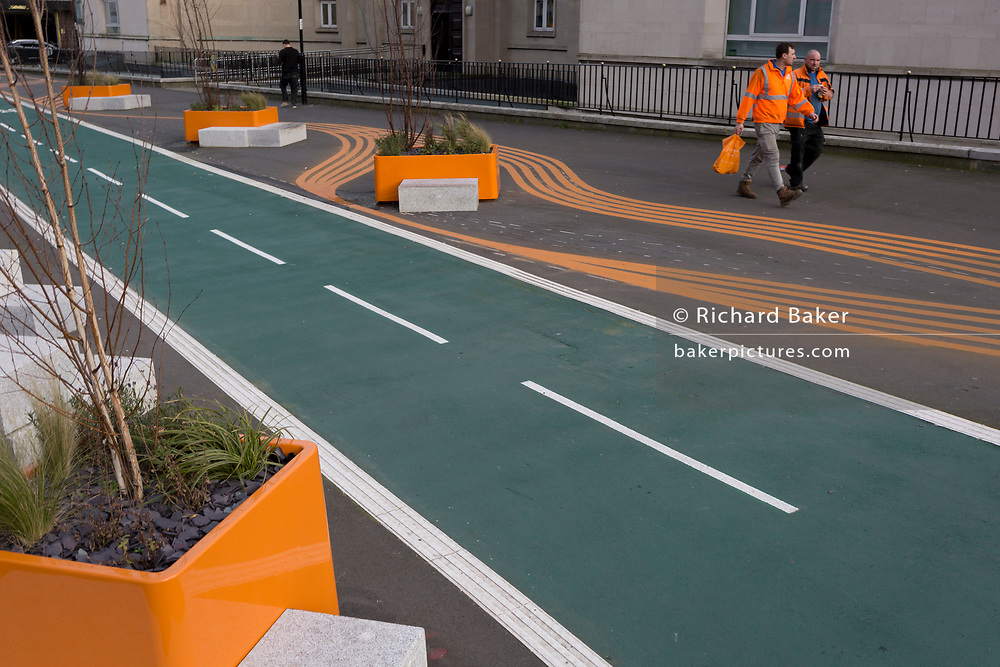 A workman carries an orange supermarket bag while walking alongside a new cycling path, a regenerated landscape created outside Croydon College and Fairfield Hall, on 20th January 2020, in Croydon, London, England.
