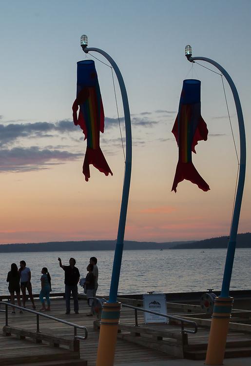 United States, Washington, Kirkland, waterfront on Lake Washington at sunset with fish flags.