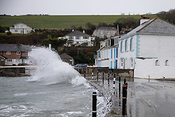 © Licensed to London News Pictures. 18/12/2020. St Austell, UK. Large surges onto the road near houses at Portmellon, Cornwall, during a storm. The south-west is experiencing strong winds of up to 60mph, and and heavy rain with flood warnings. Photo credit : Tom Nicholson/LNP