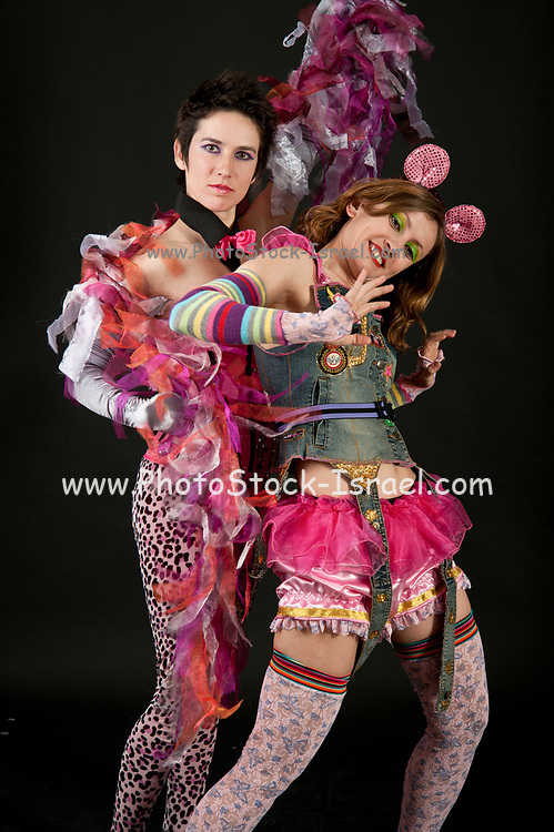 Two young women in crazy clothes fool around together