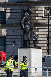 © Licensed to London News Pictures. 01/09/2020. London, UK. Police stand next to the Statue of Winston Churchill as Members of Extinction Rebellion (XR) environmental campaign group gather in Parliament Square in central London to start their sit-in this morning to blockade Parliament. XR plan to peacefully disrupt the UK Parliament with actions planned over two weeks, until MP's back the Climate Ecological Emergency Bill and prepare for crisis with a National Citizens's Assembly. Photo credit: Alex Lentati/LNP