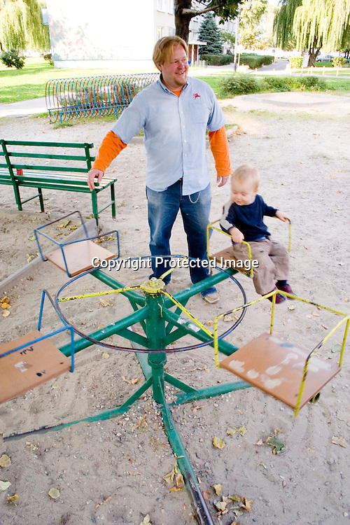 Toddler having a wonderful time on antiquated merry-go-round. Balucki District Lodz Central Poland